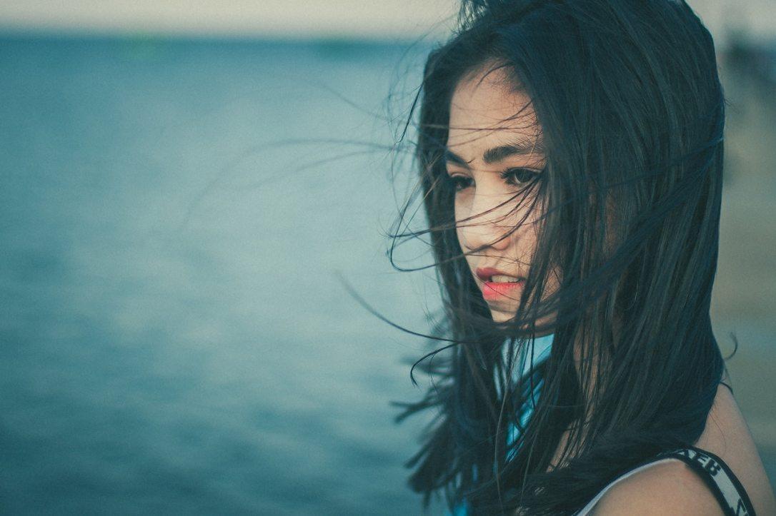 Jeune femme au bord de l'eau avec ses cheveux volants dans le vent